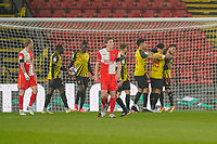 David Wheeler of Wycombe Wanderers looks despondent as Andre Gray of Watford (18) celebrates with team mates after he scores the opening goal during the Sky Bet Championship behind closed doors match between Watford and Wycombe Wanderers at Vicarage Road, Watford, England on 3 March 2021. Photo by David Horn.