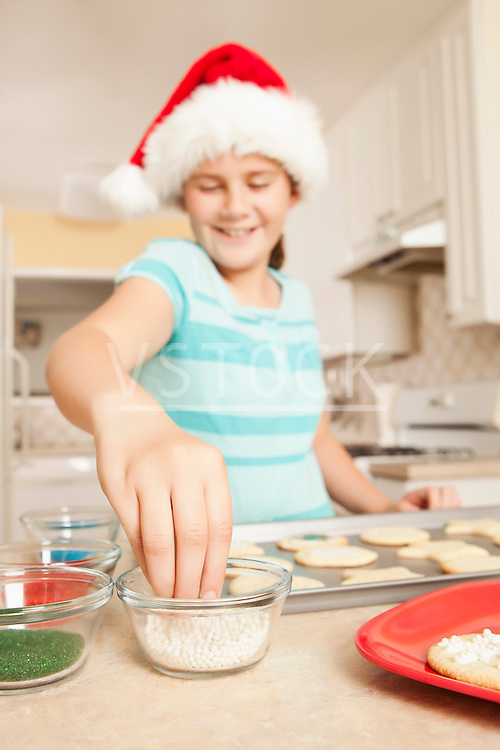 USA, California, Lawndale, Girl (10-11) wearing santa hat topping cookies with sprinkles
