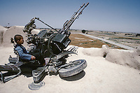 A young boy on a 23 mm towed cannon missile set ZUR-23-2S in a military base of the General Rashid Dostum, next to Mazar-e Charif..The warlord Rashid Dostum is based in northern Afghanistan, from where he still heads the Junbesh-e Melli Islami (National Islamic Movement), a predominantly Uzbek militia faction. .The veteran of many wars, he has displayed an uncanny ability to switch sides and stay on the right side of those in power. .In the 1980s Gen Dostum backed the invading forces of the Soviet Union against the mujahideen rebels. .He then played a prominent role in the civil war that destroyed much of the capital Kabul and left thousands dead. .In 2001, while helping the United States, his militias were accused of suffocating hundreds of Taleban prisoners to death by locking them inside shipping containers.