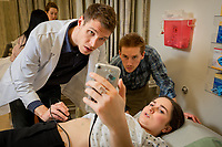 Alaska WWAMI Program medical students Evan Gross and Kenton Stephens practice using a portable ultrasound on classmate Zane Davis as their class learns the basics of ultrasound in UAA's Health Sciences Building.