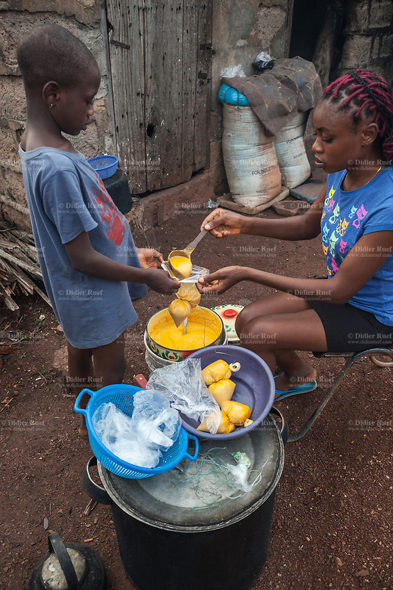 Nigeria. Enugu State. Enugu. Two Igbo sisters are cooking moimoi int the home courtyard. Moimoi or Moin-Moin is a Nigerian steamed bean pudding made from a mixture of washed and peeled black-eyed peas, onions and fresh ground peppers (usually a combination of bell peppers and chili or Scotch bonnet). It is a protein-rich food that is a staple in Nigeria. Enugu is the capital of Enugu State, located in southeastern Nigeria. 5.07.19 © 2019 Didier Ruef
