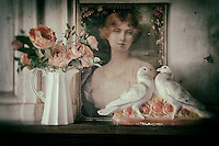 Vintage poster of a woman, jug of flowers and china ornament, processed to emulate wet plate technique.