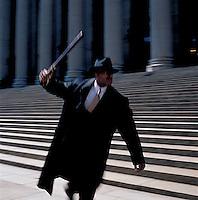 Man in suit swinging nightstick<br />