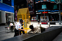 """NEW YORK, NEW YORK - SEPTEMBER 3: A security worker wakes up a homeless at Times Square on September 3, 2020 in New York.  U.S. President Trump has ordered to the federal government to begin the process to defund NYC and three other cities where protest """"lawless"""" were allowed and police budgets were cut, rising violent crime. (Photo by Eduardo MunozAlvarez/VIEWpress via GettyImages)"""