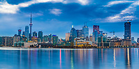 Beautiful view of Toronto city skyline from harbor piers, with buildings lit up under a cloudy sky at twilight, in Ontario province, Canada