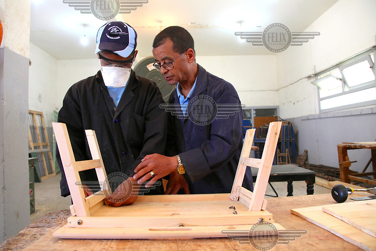 A 15 year old boy is taught wood work at the Centre de Protection d'Enfance for youths who have been in trouble with the law.