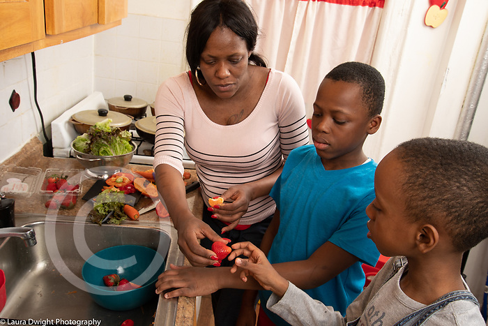 Mother in kitchen with 10 year old sons, food preparation, offering boy a strawberry, healthy snack