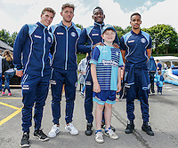 Wycombe Wanderers players pose for a photo with a young supporter wearing the team's new home kit during the 2016/17 Kit Launch of Wycombe Wanderers to the public at Adams Park, High Wycombe, England on 10 July 2016. Photo by David Horn.