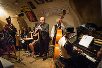 Sylvia Howard, Yves Riquet, Jean-Paul Amouroux, Jelly Germain, Nicolle Rochelle, Alain Marquet (clarinet), Bernard Brimeur (double bass) and Lou Lauprete (piano) (l to r) at a jazz concert by the Fantastic Harlem Drivers at the Petit Journal St Michel, Paris, Saturday 19th April 2014. The Fantastic Harlem Drivers consist of pianist Lou Lauprete, clarinetist Alain Marquet, double bass player Bernard Brimeur, and vocalists Sylvia Howard and Nicolle Rochelle, accompanied by tap-dancers Jelly Germain, his son Osiris Germain and Caroline Podetti. Lou Lauprete and Alain Marquet are regulars at Paris Boogie Speakeasy, the  private Parisian jazz club founded and run by Yves Riquet. Sylvia Howard sings with the Duke Ellington orchestra and the Black Label Swingtet, each led by saxophone player Christian Bonnet. Nicolle Rochelle is an internationally known singer, dancer, and actress, the star of Jerome Savary's 'Josephine' which ran for four years in France and Europe, in which Nicolle took the lead role as Josephine Baker. The evening was also attended by Yves Riquet (Sponsor and founder of Paris Boogie Speakeasy) and Jean-Paul Amouroux introduced as the finest player of Boogie-Woogie in Europe. The Fantastic Harlem Drivers were recently recorded for a new CD at Paris Boogie Speakeasy, 256 Rue Marcadet, Paris. Saturday 19th April 2014.