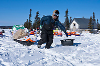 Lance Mackey hauls his supplies through the deep snow at the Cripple checkpoint to his parked dog team during the 2010 Iditarod