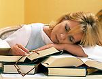 junge Frau beim Studieren ueber den Buechern eingeschlafen | young woman studying, fast asleep amongst the books