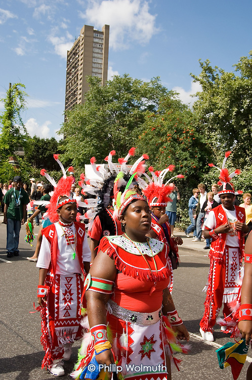 Children's day parade at Notting Hill Carnival passes Trellick Tower in North Kensington.