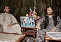 The Hizb-i-wahdat ambassador (on the right) with is assistant in Peshawar, Pakistan. .In between them, the print portrait of the actual spiritual and political leader of the Hazara people Mohammad Karim Khalili (on the right) and the former Leader Ustad Abdul Ali Mazari (on the left). ..Abdul Karim Khalili is son of Mohammad Aslam. Karim Khalili was born in 1329 H.S. (1950) in Qol-e-Khesh Behsud. It means, a part of Behsud district, province of Maidan. Today Abdul Karim Khalili is the current Leader of Hizb-e-Wahdat and Vice President of Afghanistan...Abdul Ali Mazari was born 1946 in the village of Charkint, south of the city of Mizar-i-Shrief, in northern Afghanistan, into a Hazara family. That is the reason he used surname Mazari..He studied theology in Qom, Iran. There he got involved in the Mujahideen resistance movement against the Russians in Afghanistan. He was one of the leading figures in unifying the Hazara resistance parties into one unified party, Hizb-i-wahdat (Unity Party). This party played a leading and positive role in voicing and fighting for the oppressed Hazara people of Afghanistan. During the civil war it held all the Hazara-populated areas in Afghanistan. He was highly respected figure among the Hazaras, for he had given them a voice and pride, he was affectionately called Baba (father) Mazari and Ustad (teacher) Mazari..During the siege of Kabul, the Talibans lured him for negotiations and then brutally killed him on Sunday 21/12/1373 (March 11 1995). His funeral procession march on foot from Kabul to Bamiyan and then Mazar-i-Sharif, where he was buried.