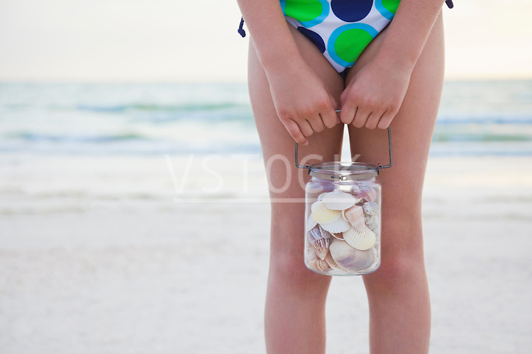 USA, Florida, St. Pete Beach, Girl (8-9) holding jar of seashells on beach, mid section