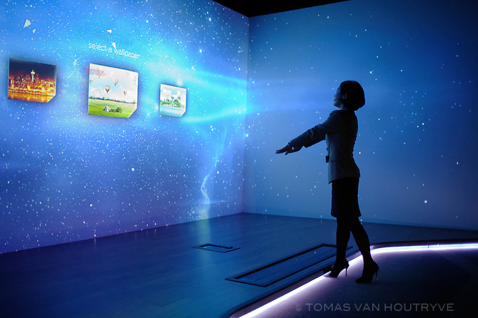 A woman uses hand gestures to change the wallpaper in an exhibition of future technology at the SK T.UM future museum in Seoul, South Korea, on Jan. 31, 2012.