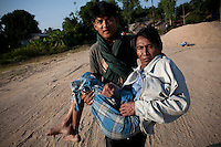 A Burmese refugee carries a family member to a boat to take them both back across the Moe Me river to Burma. After less than three days in Thailand the Burmese refugees had begun to return home. An estimated 20,000 had fled into Thailand to escape clashes in the border towns of Myawaddy and Pyaduangsu, only a day after a Burmese election which critics described as a sham..Ethnic minorities along the Thai-Burma border had warned earlier that the junta would launch a major offensive after the election, as many armed rebel groups had refused to become part of the government-controlled Border Guard Forces.