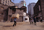 Man carrying load at city's edge; children; manpower; commerce; city of Fuling, China, Asia; old and new; 041703