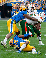 Pitt defensive players Patrick Jones (91 standing) and Phil Campbell (24) tackle a Miami ballcarrier. The Miami Hurricanes football team defeated the Pitt Panthers 16-12 in a game at Heinz Field, Pittsburgh, Pennsylvania on October 26, 2019.