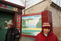 Villagers stand next to an elaborate and newly built gate in Dongzhuangying Village, on the southern outskirts of Beijing. Villagers have been building new extensions to their properties in-light of news that their village will be destroyed to make way for a new city airport. Villagers will be compensated more depending on the area of their homes, resulting in new buildings appearing across the village, as villagers anticipate higher amounts of compensation from local government. China. Friday 25th January, 2013.