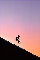 My son playing on sand dune at sunset near Florence