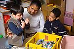 Preschool 3-5 year olds female teacher mediating dispute between two boys horizontal