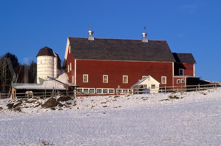 Barn and farm iwith snow covered field.