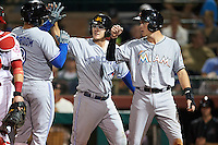 Mesa Solar Sox Ryan McBroom (9), of the Toronto Blue Jays organization, high fives teammates Danny Jansen (center), also of the Blue Jays, and Brian Anderson (right), of the Miami Marlins organization, after hitting a home run during a game against the Scottsdale Scorpions on October 17, 2016 at Scottsdale Stadium in Scottsdale, Arizona.  Mesa defeated Scottsdale 12-2.  (Mike Janes/Four Seam Images)