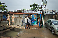 Nigeria. Lagos. Art shop. Framed painting for sale. On a rainy day, two men carried a large painting by hands and bring it inside the shop in order to protect it from the bad weather. Two caucasian manikins without clothes. A Toyota car is for sale. Lagos is a city in the Nigerian state of the same name. The city, with its adjoining conurbation, is the most populous in Nigeria and on the African continent. It is one of the fastest growing cities in the world and one of the most populous urban areas. 26.06.19 © 2019 Didier Ruef