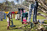 Philippines. Province Eastern Samar. Hernani. A woman with a bucket on her head hangs up her washed clothes on a rope or on trees' branches in the garden of orphanage (Nordic Harvest Bible Community Child Care Center), which served as an emergency evacuation center during Typhoon Haiyan and is now converted into a place of temporary accommodation. 95 % of the town was destroyed by typhoon Haiyan's winds and storm surge. Typhoon Haiyan, known as Typhoon Yolanda in the Philippines, was an exceptionally powerful tropical cyclone that devastated the Philippines. Haiyan is also the strongest storm recorded at landfall in terms of wind speed. Typhoon Haiyan's casualties and destructions occured during a powerful storm surge, an offshore rise of water associated with a low pressure weather system. Storm surges are caused primarily by high winds pushing on the ocean's surface. The wind causes the water to pile up higher than the ordinary sea level. 25.11.13 © 2013 Didier Ruef