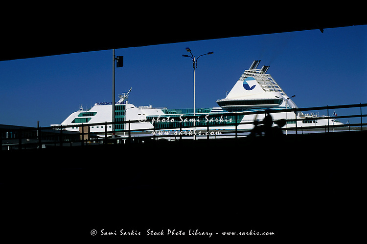 Ferry seen through silhouetted highway, Marseille, France.
