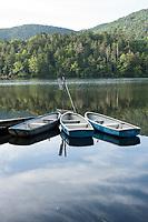 Row boats float amidst the reflections on Shirakomaike Lake in the Yatsugatake range, Nagano, Japan