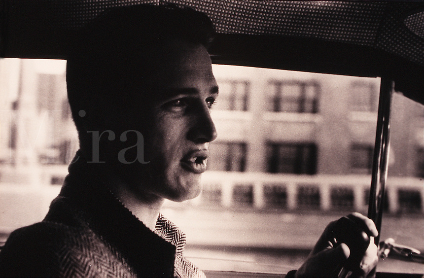 Portrait of actor Paul Newman as he sits in a car, pipe in hand as he talks. Circa 1956.