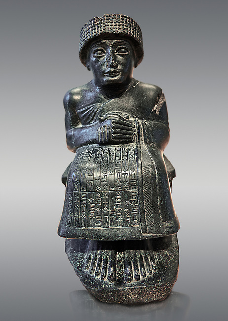 Black diorite statue of Guidea who ruled Lagash from around 2150 BC. The statue called the is dedicated to the god Ningishzida. From the ancient Sumarian city of Lagash. Louvre Museum Paris