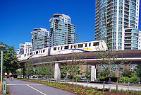 Vancouver, BC, British Columbia, Canada - Skytrain Rapid Transit System travelling past Highrise Buildings in City