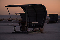 Empty curved picnic shelters are seen as sun sets at White Sands National Monument near Alamogordo, New Mexico, USA, on Fri., Dec. 29, 2017.