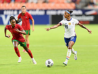 HOUSTON, TX - JUNE 10: Crystal Dunn #19 of the United States brings the ball up the field with Diana Silva #16 of Portugal closing in during a game between Portugal and USWNT at BBVA Stadium on June 10, 2021 in Houston, Texas.