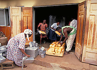 Family members prepare fresh bread in their home bakery located in Kumasi, Ghana. They'll sell it in it local markets. activities, trade, occupations, food. Family bakery in Ghana, Africa. Kumasi, Ghana home in city of African family.