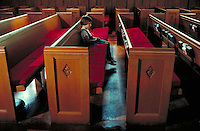 Church pews, side view, dramatic lighting and a girl sitting in the center.  May not be used in an elementary school dictionary.