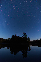 The blue starry sky reflects in the still waters of the lake, with a typical northern Ontario shoreline dark against the horizon, Balsam Lake, Ontario.