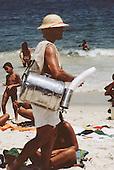 Rio de Janeiro, Brazil. Man selling matte tea from an aluminium barrel on Copacabana beach.