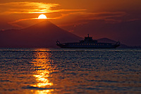 The Oropos to Eretria ferry boat sails as the sun sets -marking the longest day of the year during the summer solstice- over the seaside port town of Oropos, 30 miles (50 km) north of Athens, Greece. Friday 21 June 2019