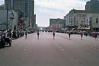 Vintage view looking south on Congress Avenue of Majorettes marching during downtown Austin parade. Image includes iconic buildings such as Piccadilly Cafeteria, State Theater, Paramount Theater, Woolworth's, Kruger's Jewelers, Kress, Stein's, Betty Lee Shoes, Lee Optical, Paris Hats, circa 1960s - Stock Image.