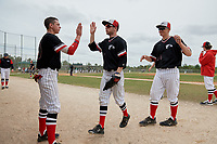 Edgewood Eagles Casey Willis (10) high fives Ryan Cassady (5) as Paul Cappetta (34) looks on during a game against the Babson Beavers on March 18, 2019 at Lee County Player Development Complex in Fort Myers, Florida.  Babson defeated Edgewood 23-7.  (Mike Janes/Four Seam Images)