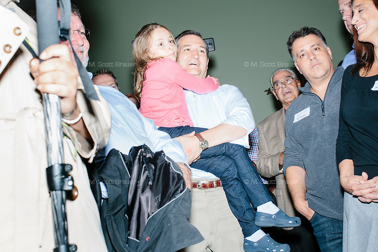 """Texas senator and Republican presidential candidate Ted Cruz holds daughter Caroline before speaking at an event called """"Smoke a cigar with Ted Cruz"""" at a house party at the home of Linda & Steven Goddu Salem, New Hampshire."""