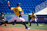 Michigan Wolverines first baseman Hector Gutierrez (24) holds Trey Martin (6) on as pitcher Tommy Henry (47) delivers a pitch during a game against Army West Point on February 17, 2018 at Tradition Field in St. Lucie, Florida.  Army defeated Michigan 4-3.  (Mike Janes/Four Seam Images)