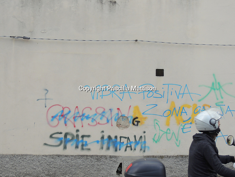 Antella, Italy - October 2, 2012: A young woman on a scooter passes a graffiti-covered wall.