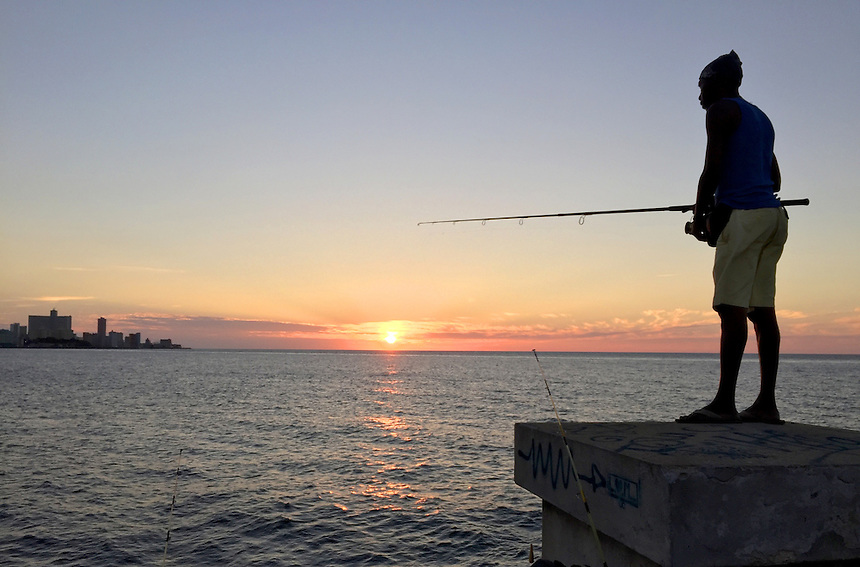 A man fishes off the Malecon at sunset in Havana, Cuba. MARK TAYLOR GALLERY