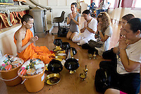 Thailand. Bangkok. Wat Saket, Golden Mount temple. A young man, fully ordained male Buddhist monastic, also called Bhikkhu, is celebrating a religious ceremony for a group of Lady's boys (transsexual), and gay men. All kneel on the floor, pray with both hands up in front of their chests and offered food gifts ( made donations) to the temple.  The monk was brought up in Wat Pho temple, which surrounds Tha Thian. 28.03.09  © 2009 Didier Ruef