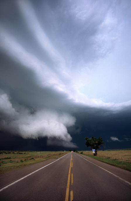 A wall cloud from an approaching severe thunderstorm is illuminated a ghostly white over a highway in western oklahoma in June.