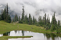 2 hikers and their reflections at alpine Upper Tipsoo Lake, with a backdrop of misty clouds at 5,400 feet elevation. Mount Rainier National Park, Washington State.....Photographed on digital media.